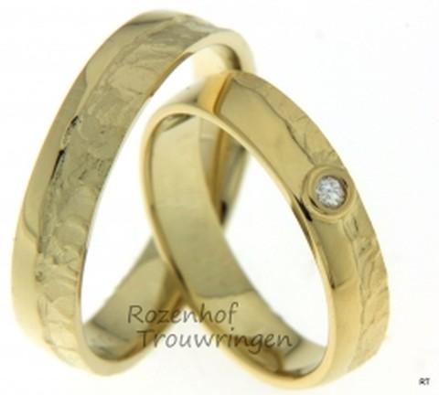 Ambachtelijke, geelgouden trouwringen met tegenstellingen. De ringen zijn 5 mm breed en hebben deels een gladde afwerking en deels een fantasievolle afwerking. In de dames trouwring prijkt een briljant geslepen diamant van 0,025 ct.