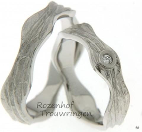 Een waar kunstwerk, deze 5,8 mm brede, grillig gevormde trouwringen van witgoud. Als een kronkelende slang vormt deze ring zich om uw vinger. In de dames trouwring is een briljant geslepen diamant gezet van 0,055 ct.