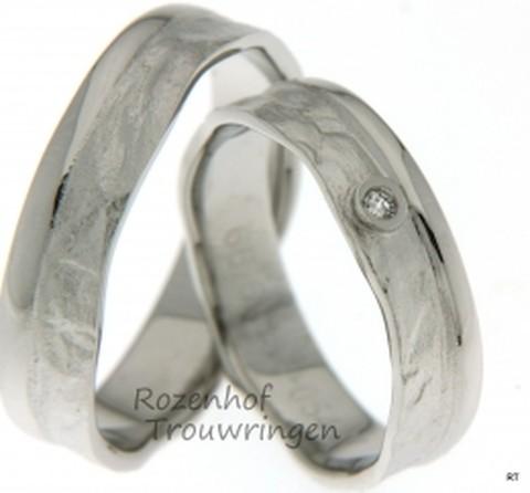 Onvoorspelbaar van karakter is deze ambachtelijke witgouden ring van 5,4 mm breed. Grillig, maar tegelijkertijd zeer gladjes. In de dames trouwring is als rots in de branding een briljant geslepen diamant gezet van 0,025 ct.