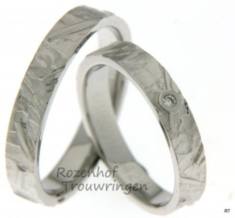Magnifiek begewerkte, ambachtelijke trouwringen van witgoud. De ringen zijn 4 mm breed en werkelijk prachtig bewerkt. De fonkelende, briljant geslepen diamant laat de bewerking nog meer spreken.