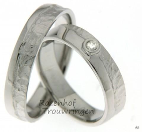 Ambachtelijke, witgouden trouwringen met speelse afwerking. De ringen zijn 5 mm breed en hebben deels een gladde afwerking en deels een fantasievolle afwerking. In de dames trouwring prijkt een briljant geslepen diamant van 0,025 ct.