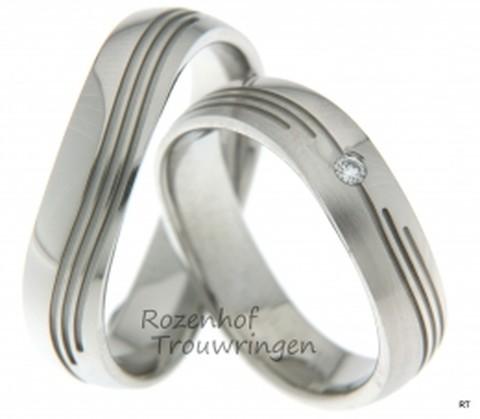 Unieke trouwringen door hun vorm en grillige lijnenspel. De ringen zijn vervaardigd uit witgoud en zijn 5,2 mm breed. In de dames trouwring prijkt een briljant geslepen diamant van 0,037 ct.