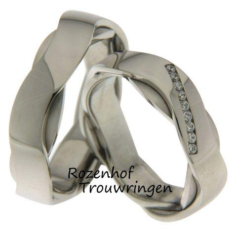 Double luck, witgouden trouwringen van 6 mm breed. De twee kronkelende, witgouden trouwringen zijn over elkaar gezet. In de dames ring zijn 9 briljant geslepen diamanten in een schuine streep in de ring gezet.