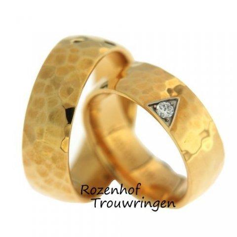 Gehamerde, tweekleurige trouwringen. De prachtige geelgouden trouwringen met hamerslag afwerking hebben een breedte van 7,3 mm. In de dames trouwring is in een witgouden driehoek een schitterende, briljant geslepen diamant gezet van 0,07 ct.