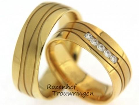 Geelgouden trouwringen met deinende lijnen. De stoere ringen zijn 7 mm breed. In de dames trouwring deinen 5 briljant geslepen diamanten mee op de belijning. Een schitterend gezicht!