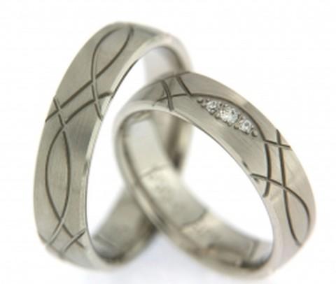 Dynamische, 5,5 mm brede, trouwringen van witgoud. De temperamentvolle lijnen geven de sfeer van deze ring weer. In de dames trouwring houdt een symbolisch oog van 3 briljant geslepen diamanten in de gaten of dit alles niet de spuigaten uitloopt.