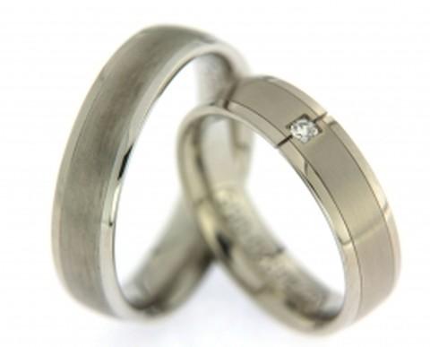 Trendy, witgouden trouwringen van 5,5 mm breed. In de dames trouwring is een fonkelende, briljant geslepen diamant gezet van 0,045 ct.