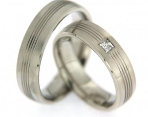 Verfijnd belijnde, witgouden trouwringen van 6 mm breed. In de dames trouwring pronkt een princess geslepen diamant.