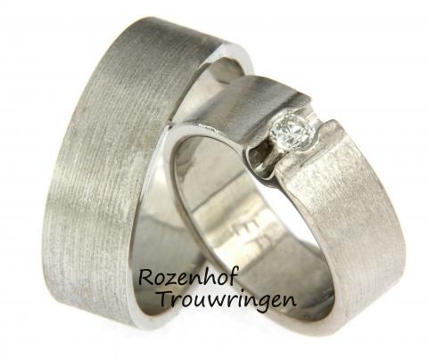 Deze stoere, maar tegelijk ook super chique ringen zijn vervaardigd uit witgoud. Wat deze trouwringen zo stoer maakt is de breedte, maar die schitterende diamant maakt de ring weer super chique. Verder is de diamant briljant geslepen en in het midden van de ring voor haar gezet.