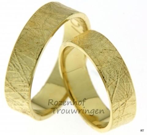 Ambachtelijke geelgouden trouwringen met een aards karakter. Het vloeibare goud van deze trouwringen lijkt na afkoeling gekristalliseerd te zijn tot een aards patroon. Ruw, maar toch verfijnd. De ringen zijn 6,1 mm breed.