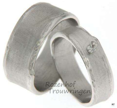 Spraakmakende, ambachtelijke trouwringen van witgoud. De ringen zijn verkrijgbaar in 6 en 9 mm breed. De binnenband is satijnmat afgewerkt met een lichte rimpeling, de smalle buitenranden zijn glanzend en grillig van vorm. In de dames trouwring schittert een briljant geslepen diamant.