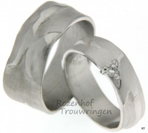 Organisch gevormde, ambachtelijke trouwringen van witgoud. In de dames trouwring zijn in een driehoeksvorm briljant geslepen diamanten gezet.