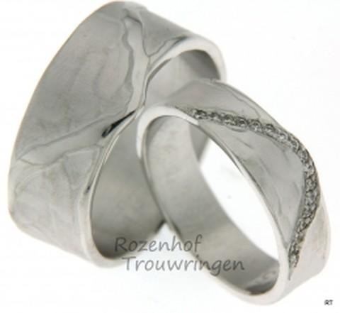 Kunstzinnige trouwringen van geelgoud met schitterende golving. De ambachtelijke ringen zijn 5,5 mm breed. De dames trouwring is bezet met een schitterende golf van 16 briljant geslepen diamanten van 0,007 ct.