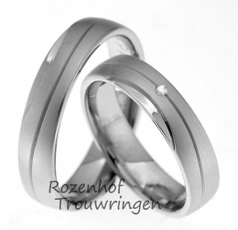 Witgouden, 5 mm brede ,witgouden trouwringen met groef rondom de ring. Een smalle hoogglans halvemaansfiguur is aan de buitenkant van de ring geplaatst. De figuurlijke zon in de damestrouwring is een briljant geslepen diamant van 0,02 ct.