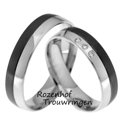 Mysterieuze trouwringen van glanzend witgoud met ruthenium. De ringen zijn 5 mm breed. In de dames trouwring schitteren 3 briljant geslepen diamanten van in totaal 0,045 ct.