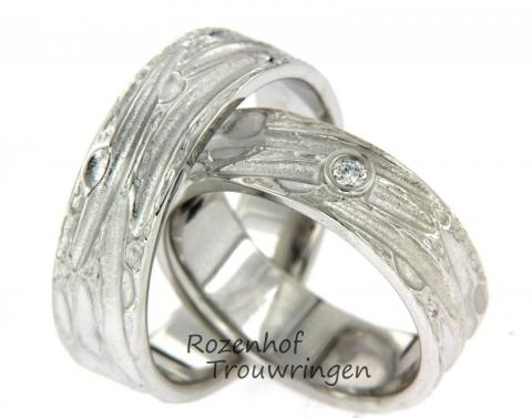 Prachtige trouwringen. de trouwringen zijn gemaakt van witgoud in een ambachtelijke stijl. In de damesring vindt een reusachtige, sprankelende diamant plaats. Deze prachtige diamant is briljant geslepen.