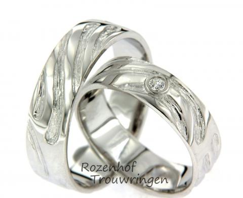 Deze glanzende trouwringen zijn uitgevoerd in witgoud en hebben een breedte van 6,1 mm.De ringen zijn gemaakt in een ambachtelijke stijl. In de damesring is een sprankelende diamant gezet van 0,045 ct. Deze diamant is briljant geslepen en staat centraal in de ring. Deze trouwringen zijn ook leverbaar in palladium of platina.