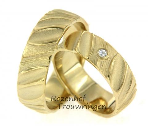 Deze mooie trouwringen in een ambachtelijke stijl zijn uitgevoerd in geelgoud. De breedte van de ring is 6,8 mm. In de damesring is één diamant gezet van 0,04 ct. Deze prachtige diamant is briljant geslepen. Dit setje is leverbaar in 9, 14 en 18 karaat goud en klaar om gedragen te worden door een verliefd stelletje!