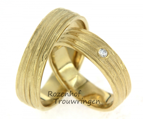 Deze mooie trouwringen zijn uitgevoerd in mat geelgoud in een breedte van 5,7 mm. De ringen hebben een mooie, rustgevende uitstraling. In de dames ring is een briljant geslepen diamant gezet van 0,04 ct. Deze ringen zijn leverbaar in 9, 14 en 18 karaat goud.