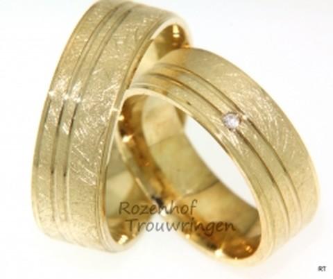 Stoere, geelgouden trouwringen van 7 mm breed, afgewerkt in ijsmattering. De dames trouwring is bezet met 1 briljant geslepen diamant van 0,02 ct.