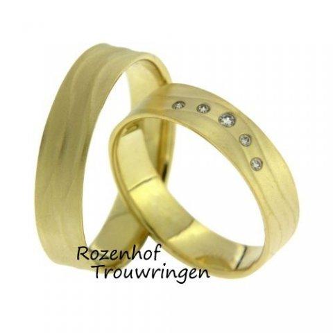 Warme geelgouden ringen met swingende golving. De ringen zijn 5 mm breed. In de dames trouwring deinen 5 briljant geslepen diamanten, van in totaal 0,035 ct, op de golving mee.