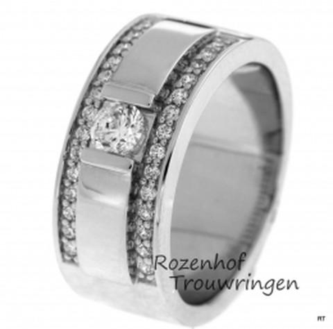 De kanjer onder de verlovingsringen. Deze ring is maar liefst 8,5 mm breed. In het midden van de ring prijkt een grote briljant geslepen diamant als een koningin op haar troon, als lakeien zijn aan weerszijden van de koningin twee rijen van elk 14 lakeien gezet.