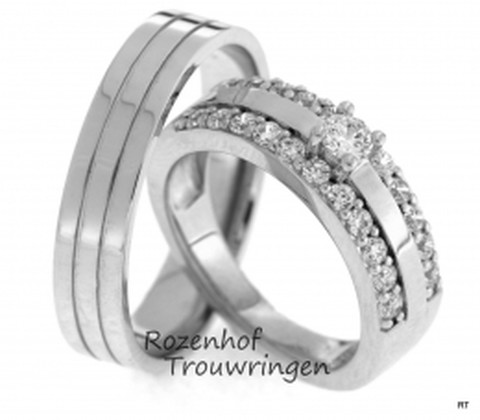 Luxueuze, witgouden trouwringen. De ring is verdeeld in drie strakke banen. De dames trouwring is bezet met 23 briljant geslepen diamanten, waaronder 1 grote diamant van 0,16 ct en 22 kleinere diamanten van 0,02 ct.