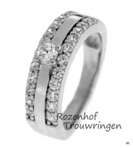 Majestueuze verlovingsring van witgoud. De ring is 6,3 mm breed en heeft aan twee zijden een railzetting met in totaal 22 briljant geslepen diamanten van 0,02 ct. Als een vorstin prijkt de grote diamant van 0,16 ct, bovenop de ring.