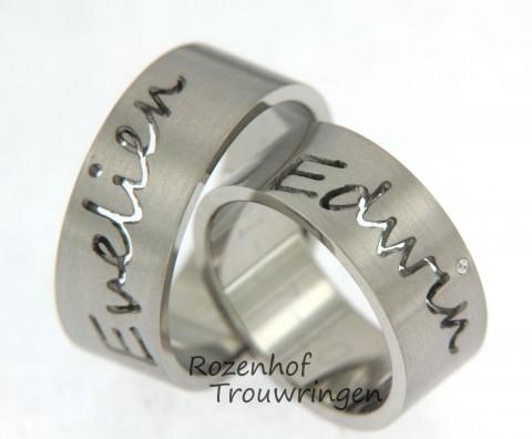 Strakke naamringen van witgoud. In de dames trouwring is een briljant geslepen diamant gezet.